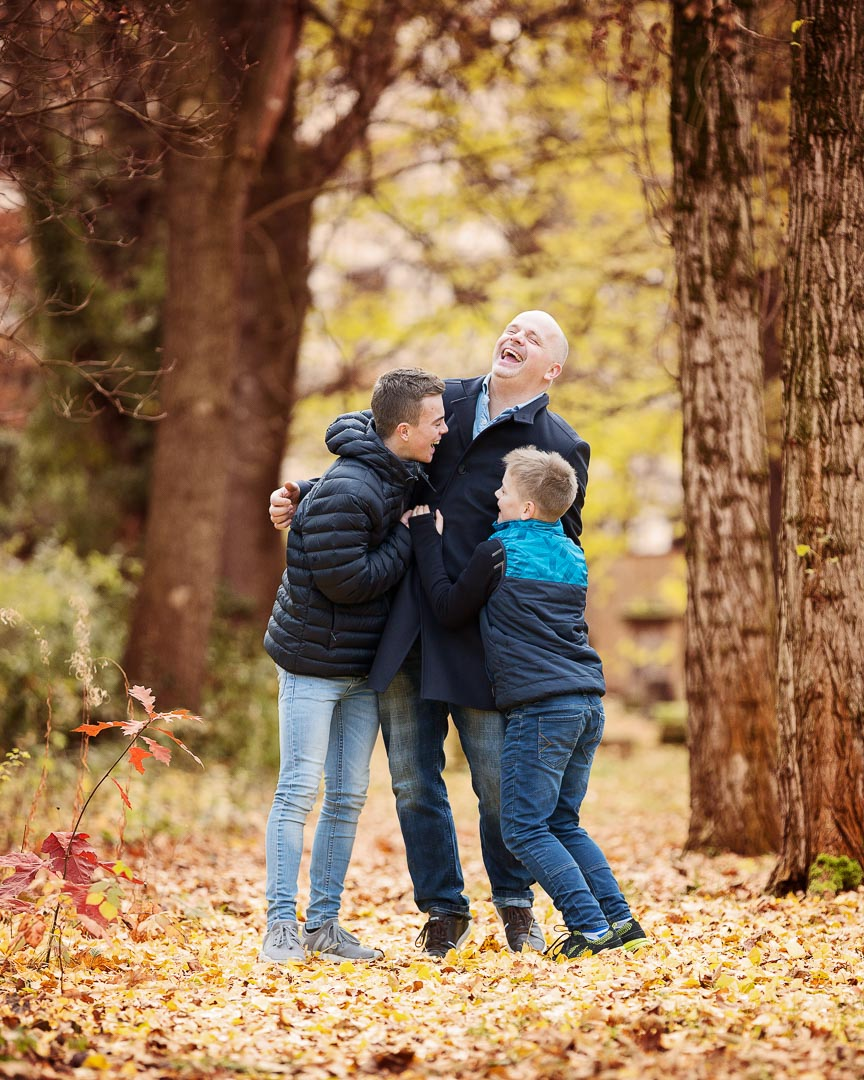 two boys tickling their dad and all laughing really hard, in a park surrounded by beautiful fall leaves