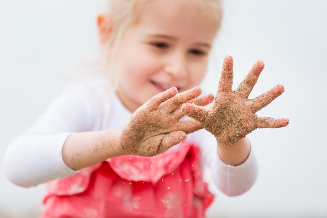 girl with hands full of sand