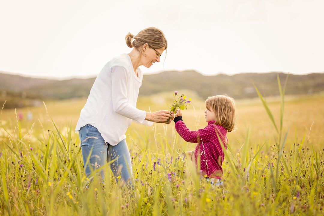 Mum plucking flowers with her daughter