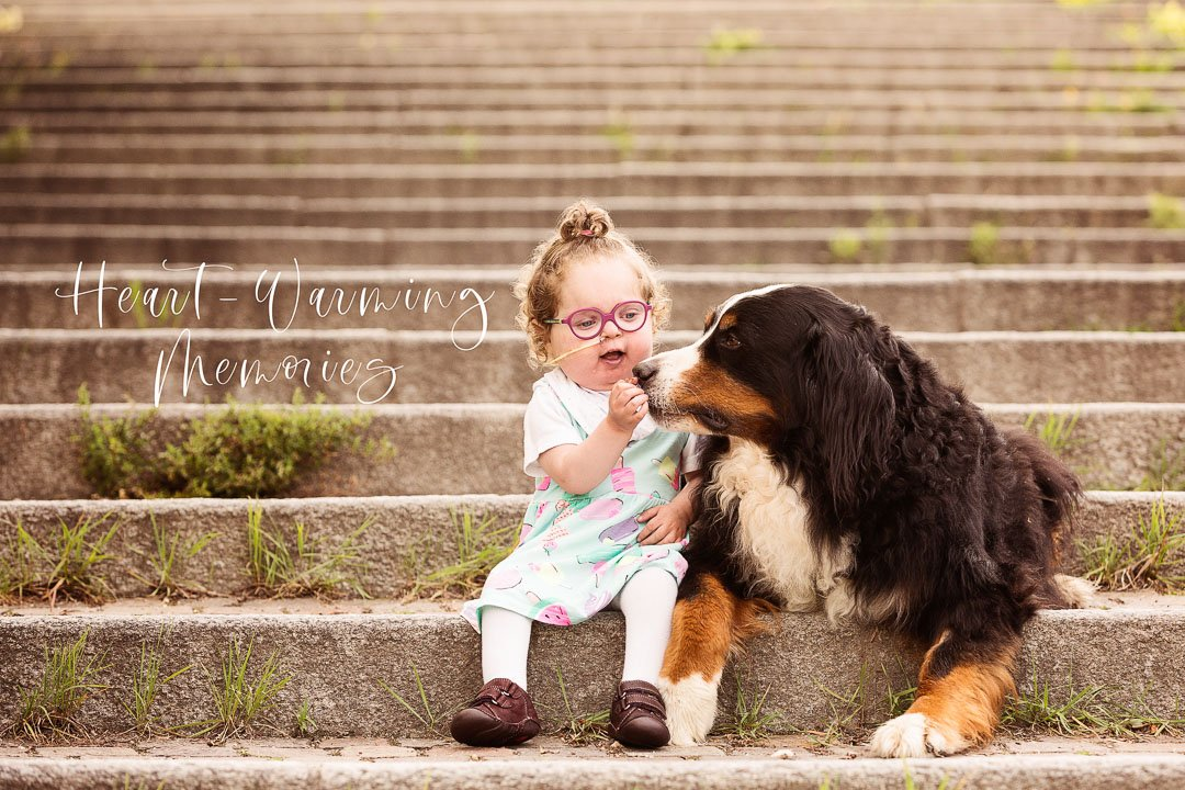 Baby girl with Bernese mountain dog