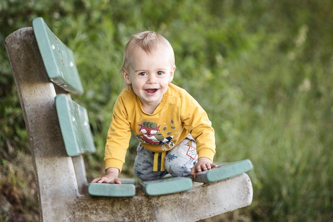 kleiner Junge klettert auf Bank in Bassersdorf