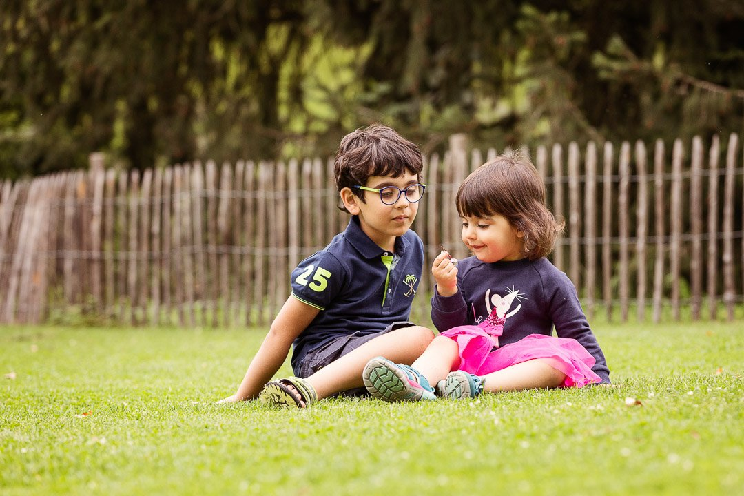 Siblings playing in the grass at Rieterpark