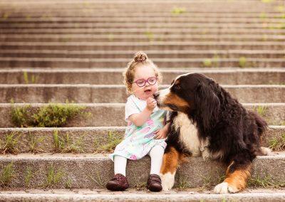 Baby girl with congenital heart disease cuddling her Bernese mountain dog