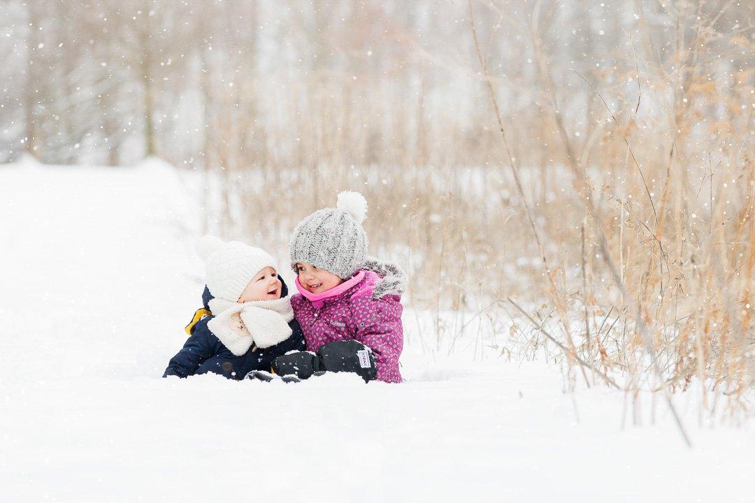 Siblings cuddling in the snow