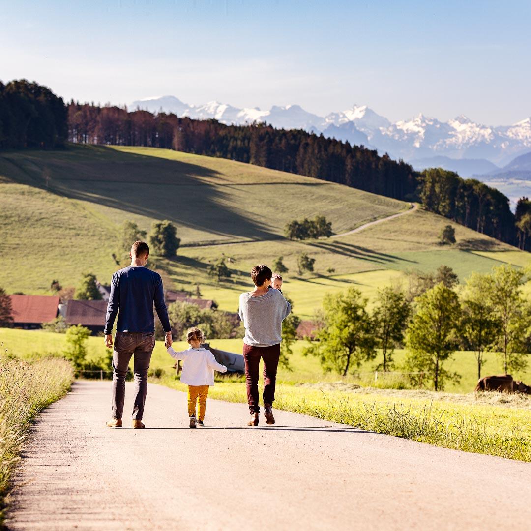 Famile spaziert am Albispass mit Glarner Alpen im Hintergrund