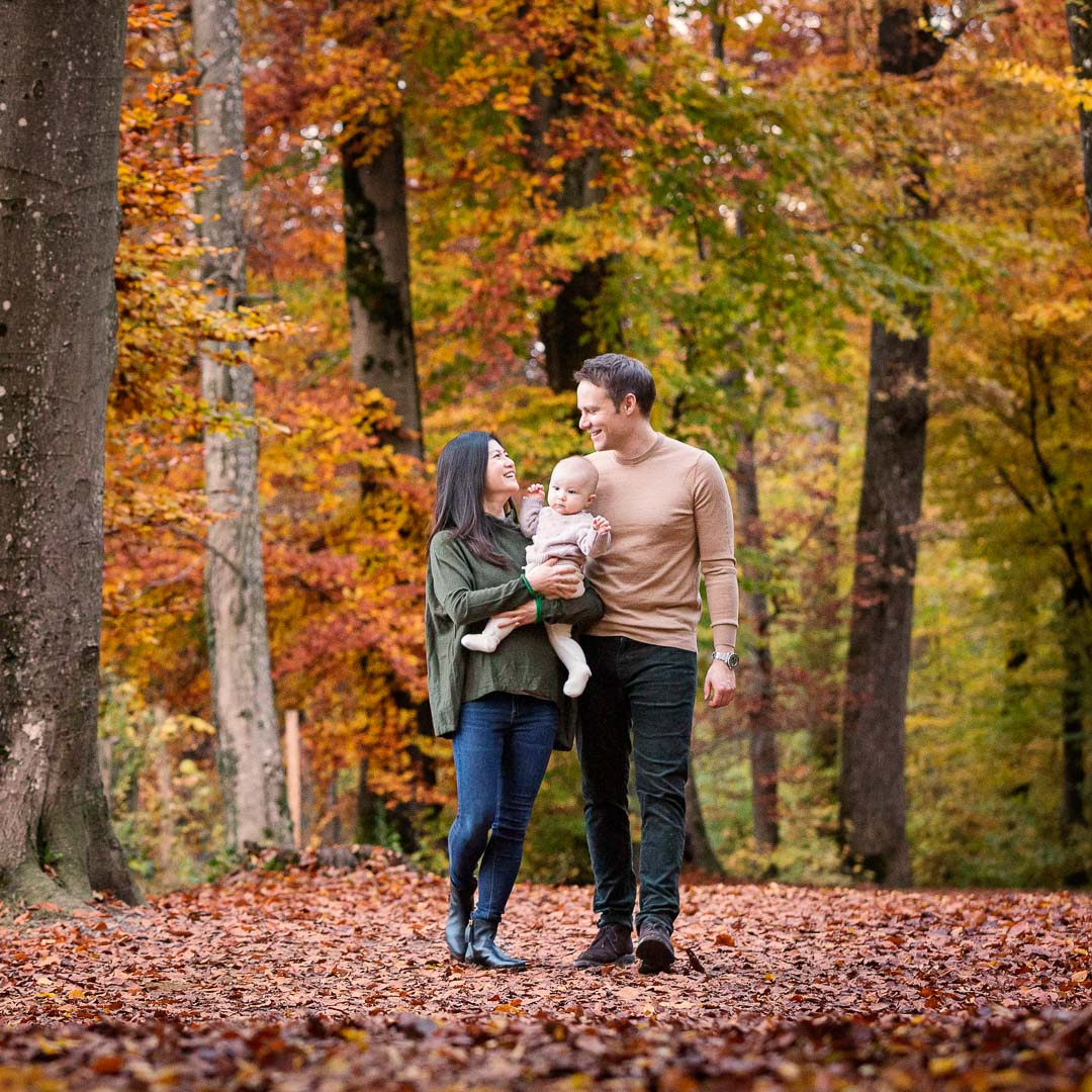 Parents with child walking in park in fall