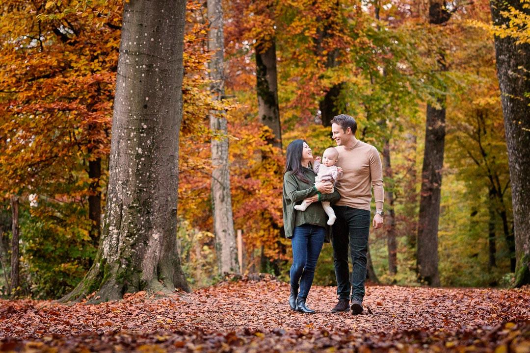 Familie mit einem Kind spaziert im Herbstwald
