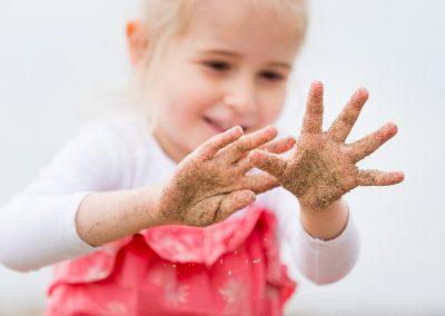 Mädchen mit Händen voller Sand