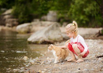 Kleines Mädchen am Strand streichelt eine Katze
