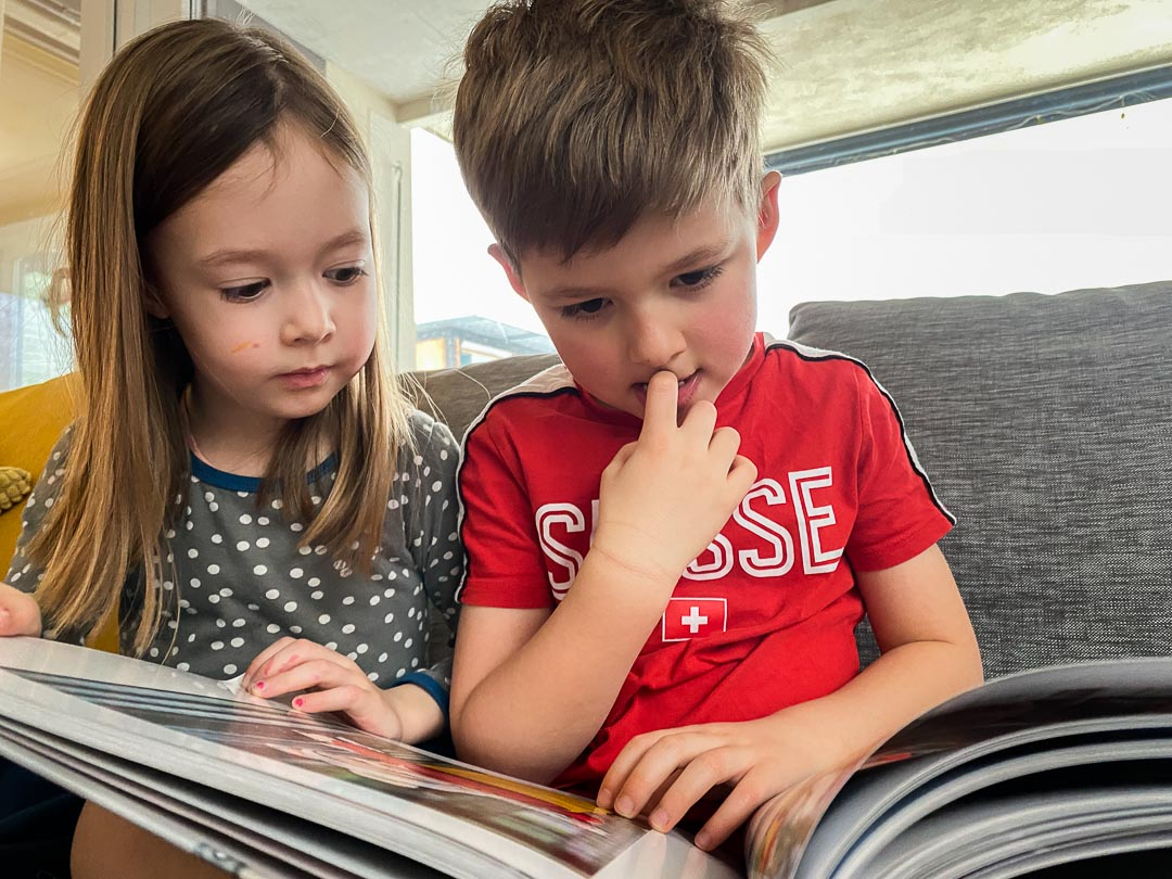 Close up of two children reading a book